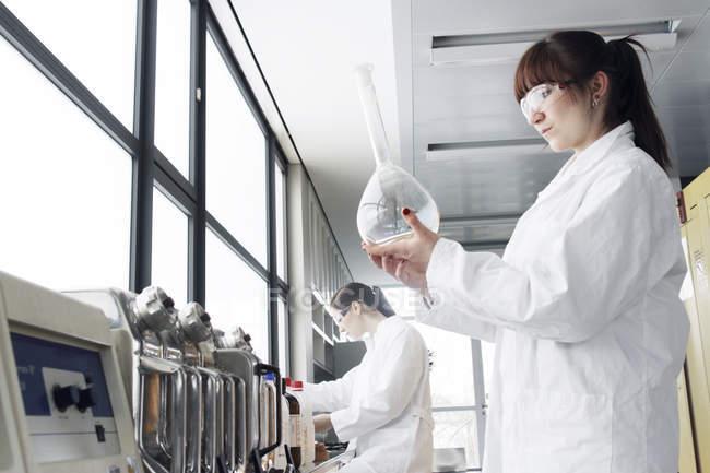 Две молодые студентки-химики в лаборатории — стоковое фото