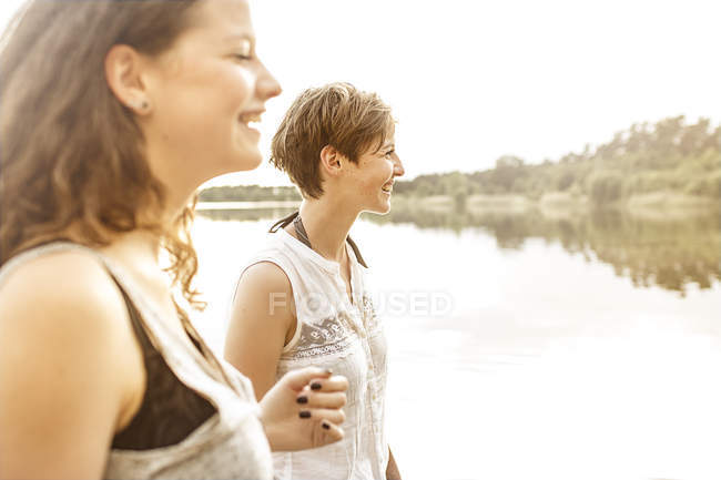 Portrait of two young women having fun at quarry pond — Stock Photo