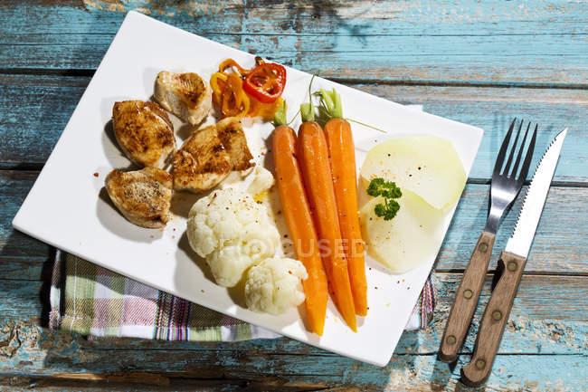 Vista elevada de rebanadas de filete de pollo con coliflor, zanahorias y pimiento morrón en el plato - foto de stock