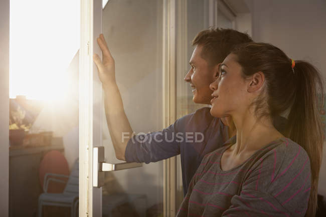 Casal em pé na janela aberta olhando para a luz do sol — Fotografia de Stock