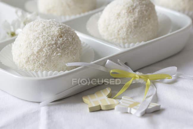 Сніжний ком тістечка з кокосова стружка на білий пластини з декор — стокове фото