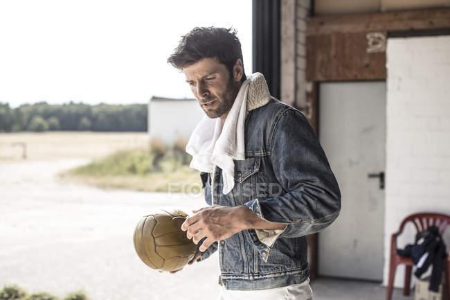 Stylish thoughtful man holding football — Stock Photo