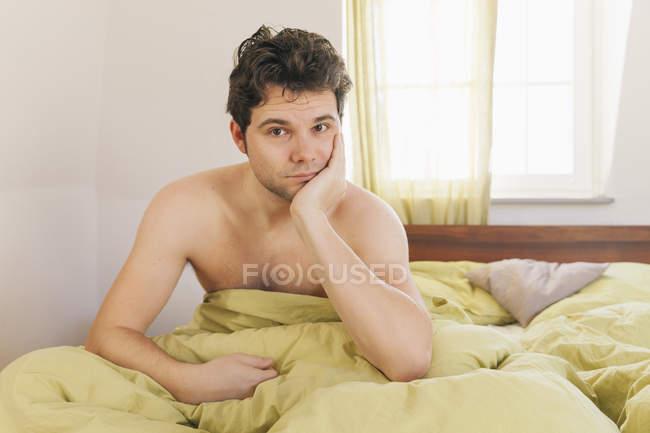 Retrato de homem sem camisa, sentado na cama — Fotografia de Stock