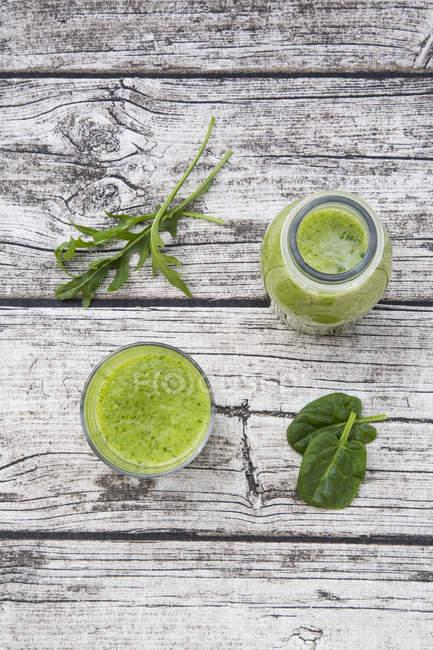 Стекло и бутылка зеленые фрукты льстец со шпинатом, ракетно салат и на серый деревянный стол — стоковое фото