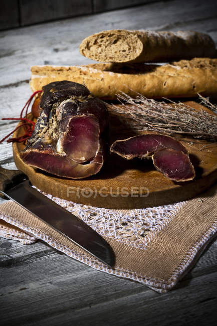 Smoked ham and onion baguette on wooden board — Stock Photo
