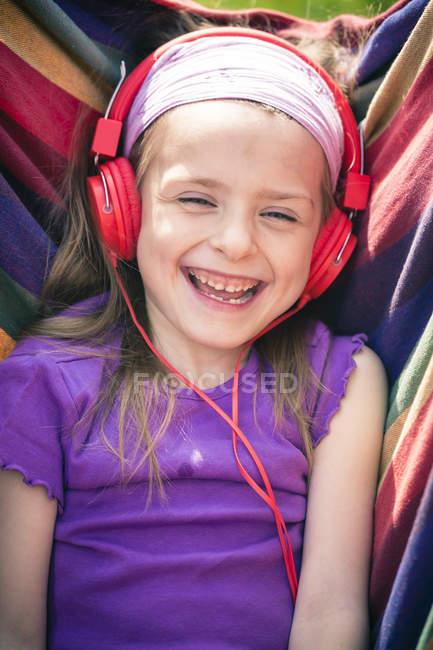 Retrato de niña riendo con auriculares rojos - foto de stock