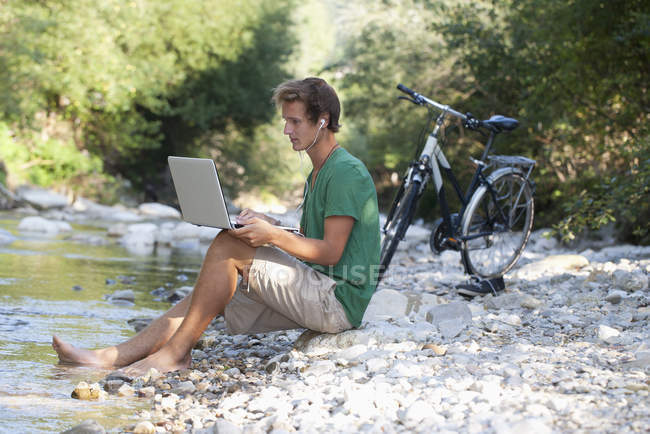 Австрія, Зальцкаммергут, Мондзю, молода людина з ноутбуком, навчання в за Брук — стокове фото