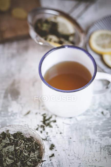 Tasse de thé à la menthe gingembre et les feuilles de menthe séchées dans un bol — Photo de stock