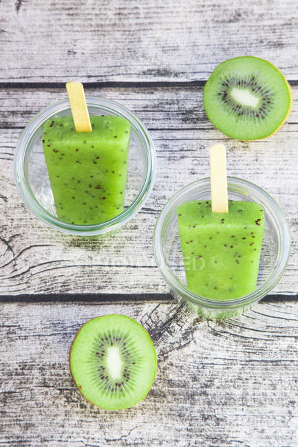 Two glasses with kiwi cream ice lollies and two halves of kiwi on grey wood — Stock Photo