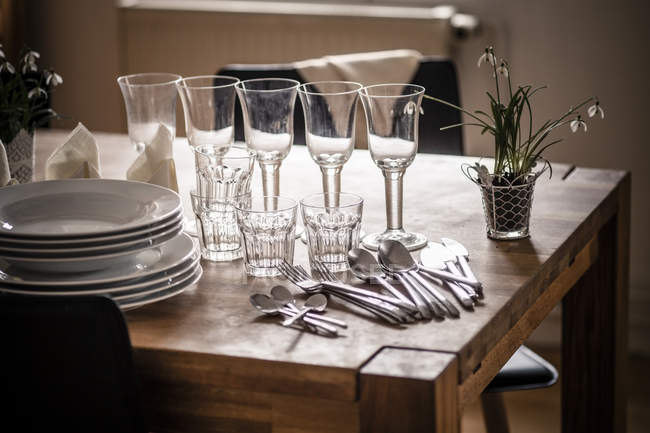 Dishes and glasses on wooden table in kitchen — Stock Photo
