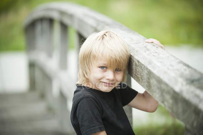 Portrait de petit garçon debout sur une promenade en bois — Photo de stock