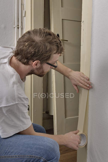 Young man masking door frame with adhesive tape — Stock Photo