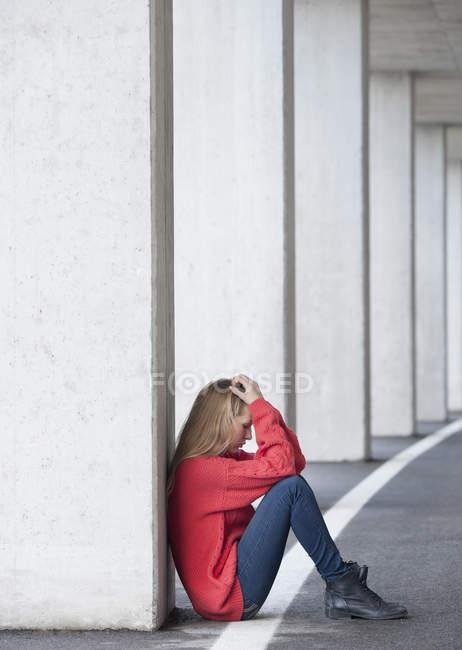 Retrato de menina adolescente infeliz sentado no chão no parque de estacionamento — Fotografia de Stock