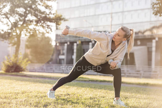 Young woman exercising with dumbbells in city — Stock Photo