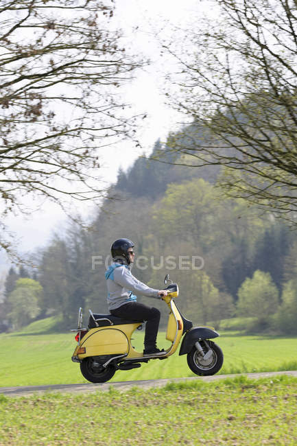 Young man driving with his motor scooter on road — Stock Photo