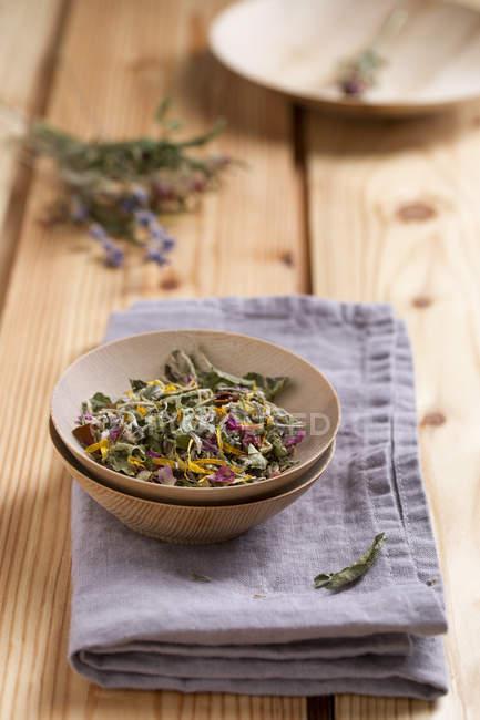 Thé de fines herbes dans un bol sur une surface en bois avec tissu — Photo de stock