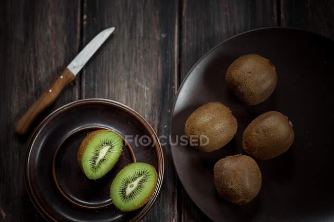 Platten aus ganze und halbierte Kiwis und Messer auf dunklen Holztisch — Stockfoto
