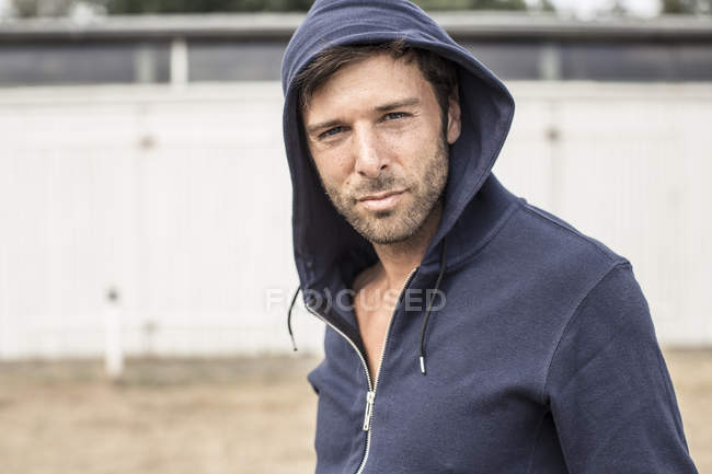 Portrait of man wearing hooded jacket looking at camera — Stock Photo
