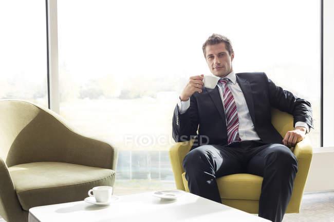 Uomo d'affari che si prende una pausa caffè nella lounge dell'hotel — Foto stock