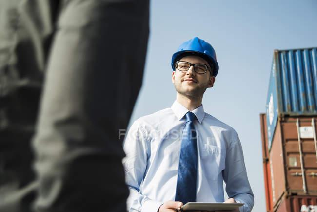 Portrait d'un homme d'affaires parlant à un adolescent au terminal à conteneurs — Photo de stock