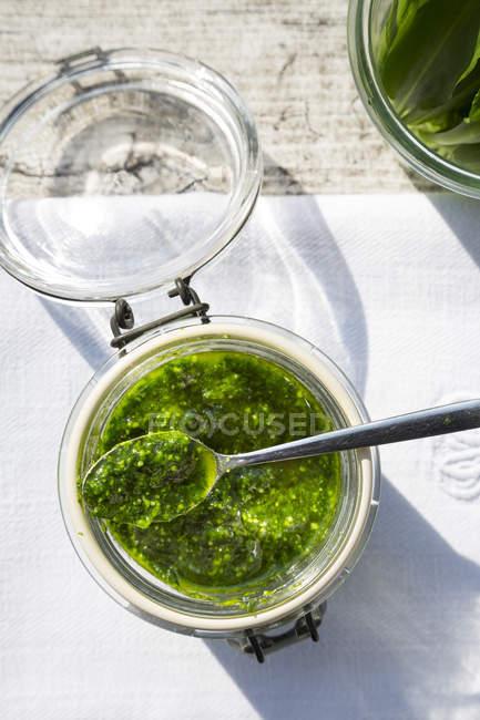 Preserving jar of basil garlic pesto on napkin and grey wooden table, top view — Stock Photo