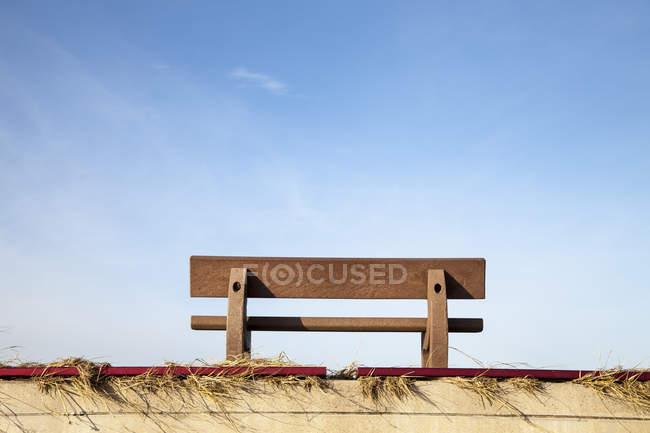 Germany, Lower Saxony, Dornum, wooden bench at waterfront promenade — Stock Photo