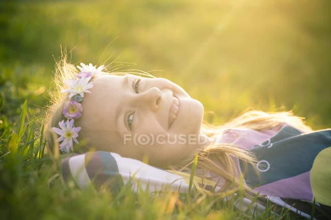 Портрет усміхнений дівчинка, лежачи на луг носіння квіти — стокове фото