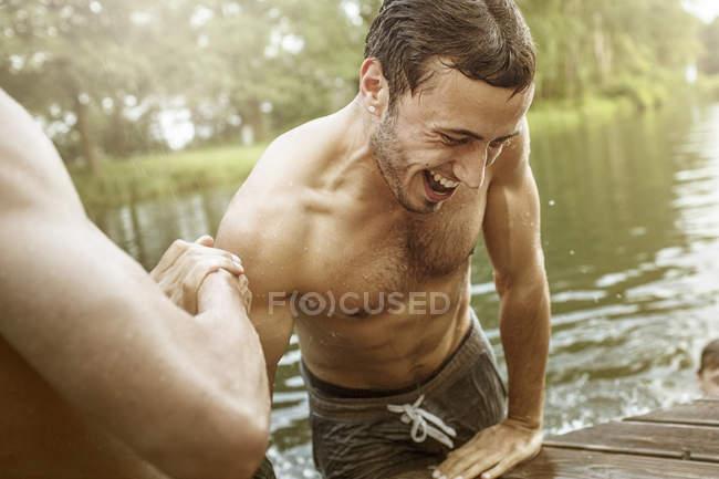 Junger Mann hilft seinem Freund gehen aus Baggersee — Stockfoto