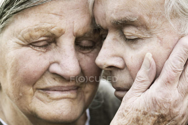 Portrait of senior couple head to head with closed eyes — Stock Photo