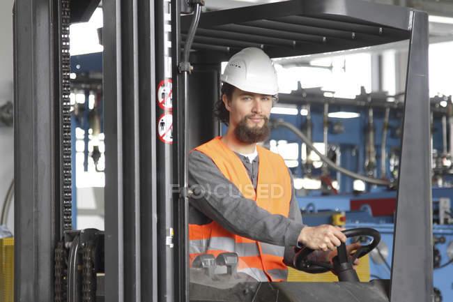 Worker with hard hat in a factory hall driving forklift — Stock Photo