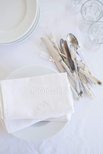 Glasses, plates, silver cutlery and cloth napkins on white table cloth, elevated view — Stock Photo