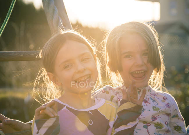 Portrait of two laughing little girls at sunset — Stock Photo