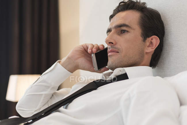 Business man lying in hotel bed telephoning with smartphone — Stock Photo