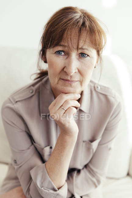 Portrait of mature woman with hand on the chin — Stock Photo
