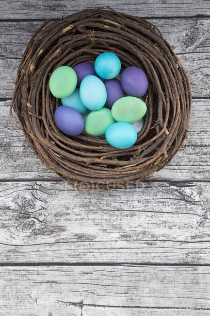 Tingido de ovos coloridos de éster no ninho na mesa de madeira cinza — Fotografia de Stock