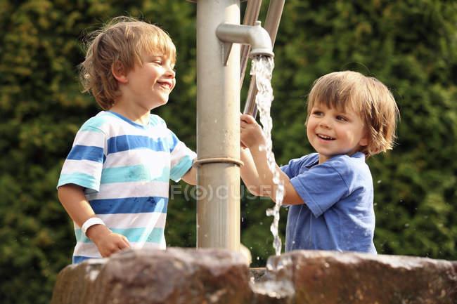 Dois meninos brincando com bomba de água — Fotografia de Stock