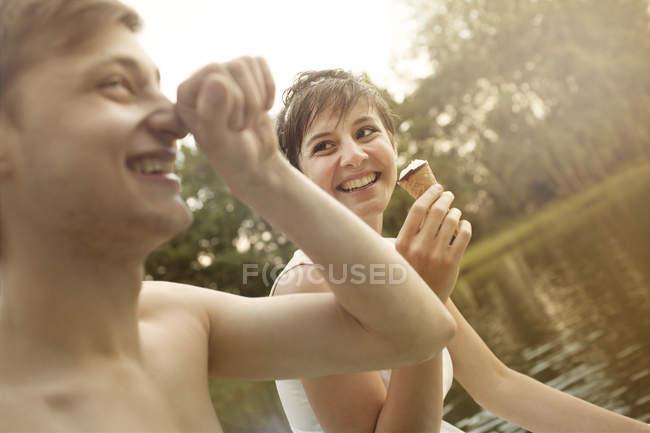 Giovane coppia si diverte a cava stagno, donna con gelato — Foto stock