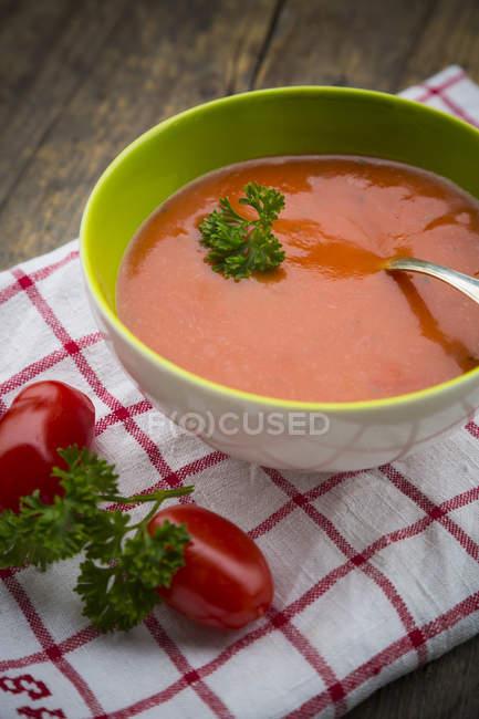 Schüssel mit Tomatensuppe und frischen Tomaten auf Küchenpapier — Stockfoto