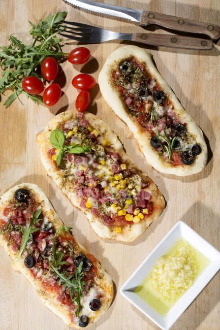 Small Pizzas with ham, salami, mozzarella, tomato, arugula, maize and olives on wood — Stock Photo
