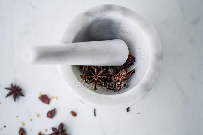 Marble mortar and pestle with star anise, top view — Stock Photo