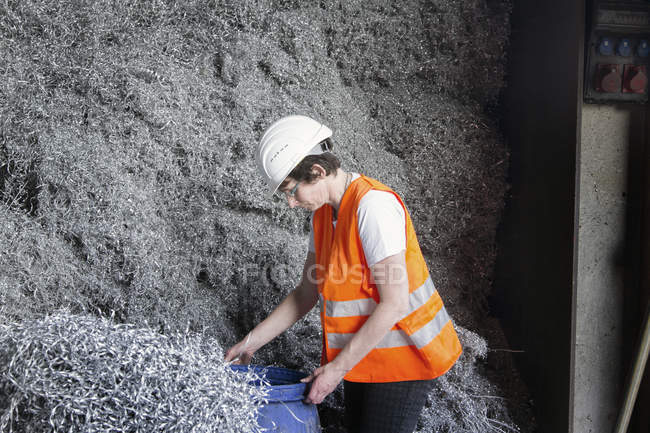 Female technician testing material at recycling yard of aluminium — Stock Photo