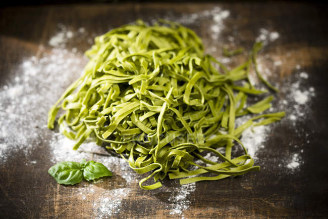 Fresh Tagliatelle Spinaci, leaves of basil and flour on wooden table — Stock Photo