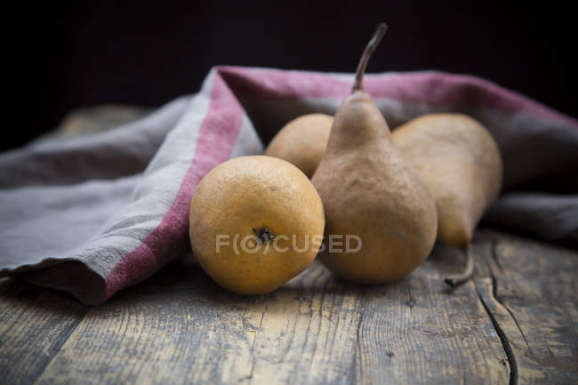 Whole fresh pears and kitchen towel on dark wood — Stock Photo