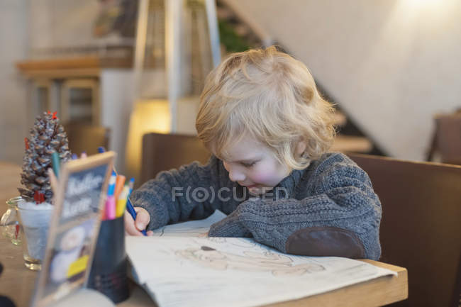 Blond boy in a cafe drawing — Stock Photo