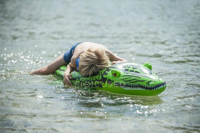 Jovem rapaz com ter um descanso no seu brinquedo de natação — Fotografia de Stock