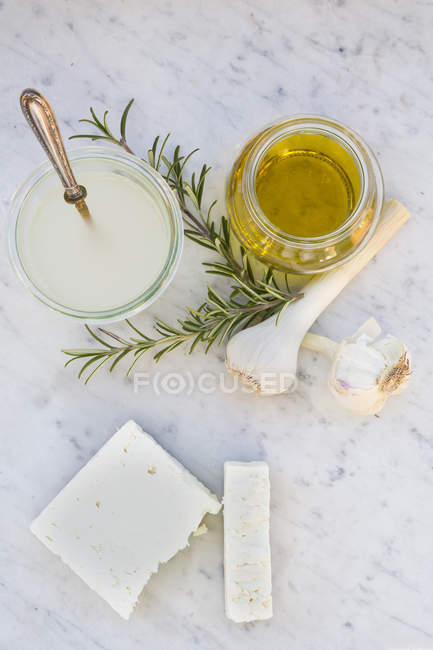 Two pieces of sheep cheese, glass of olive oil, garlic bulbs, rosemary and glass of brine on white marble — Stock Photo