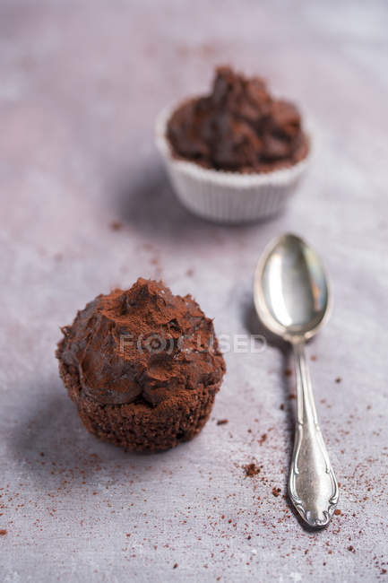 Close-up of two chocolate cup cakes and tea spoon on cloth — Stock Photo