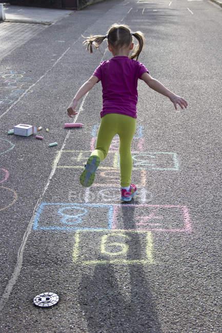 Little girl playing hopscotch — Stock Photo