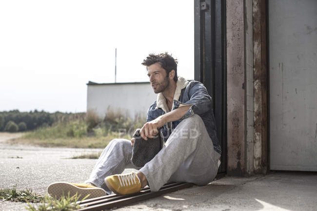 Man sitting on ground and holding woolly hat — Stock Photo