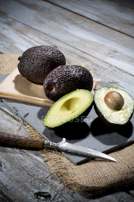 Halbierte und ganze Avocado — Stockfoto